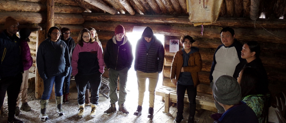 A group of diverse students touring traditional village structures at the Alaska Native Heritage Center