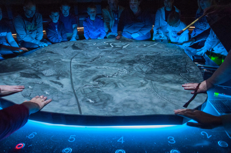 Blue-lit people standing around a 3d map at Bannockburn Battlefield