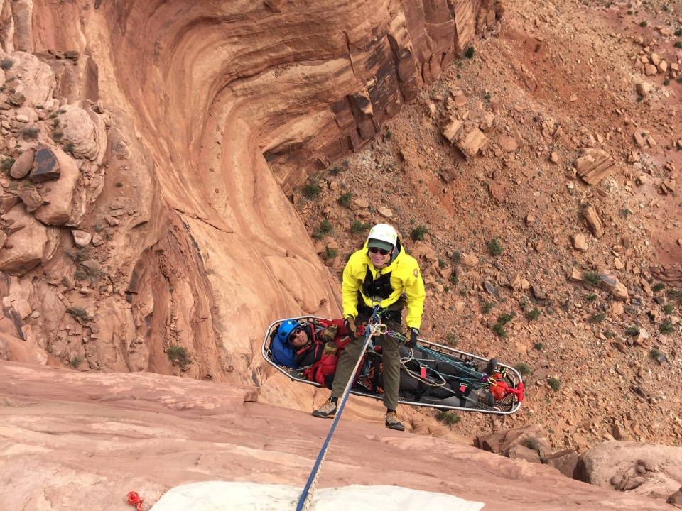 A man on a rope in a canyon with another person hanging in litter a to simulate a vertical rescue situation