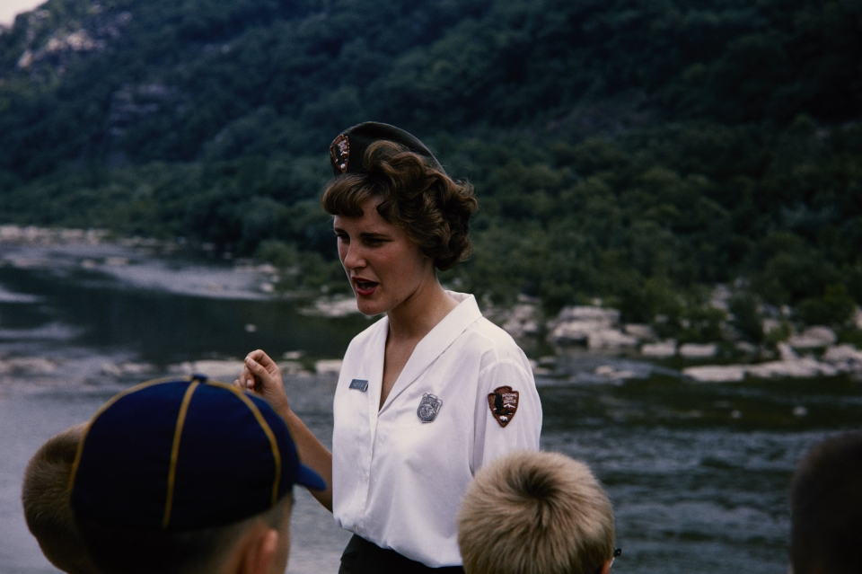 NPS employee in 1964 uniform leading a tour on a boat in Harpers Ferry National Historical Park