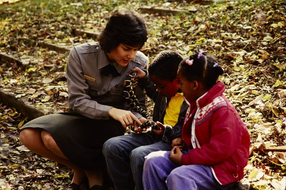 NPS employee, in uniform, sits with two young visitors, holding a snake