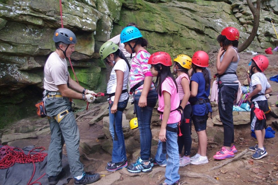 A group of kids in helmet learning how to rock climb from a park ranger at Obed Wild & Scenic River