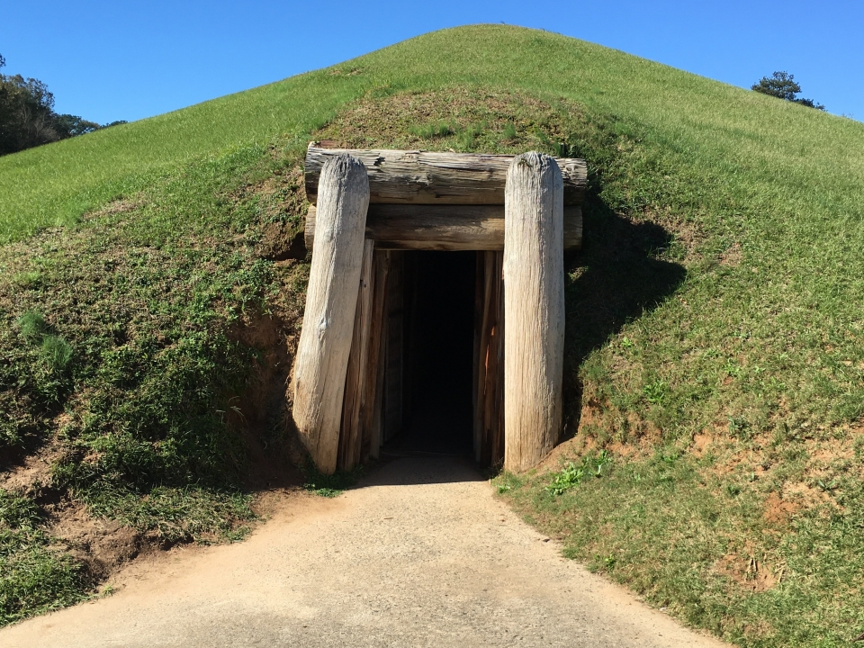 Beneath a grassy mound, wooden beams form the entrance of the Earth Lodge at Ocmulgee National Monument