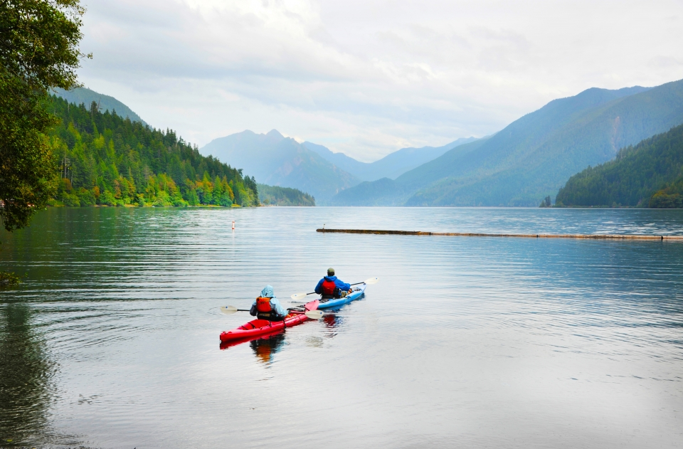 Two people in kayaks paddling through Olympic National Park