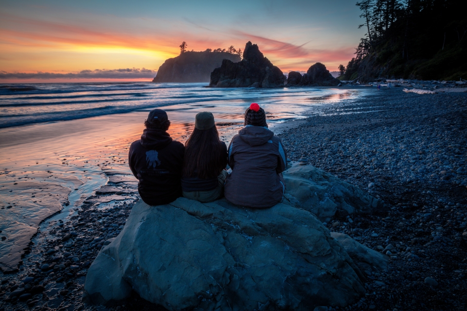 Three family members sit on a rock enjoying a sunset at Olympic National Park