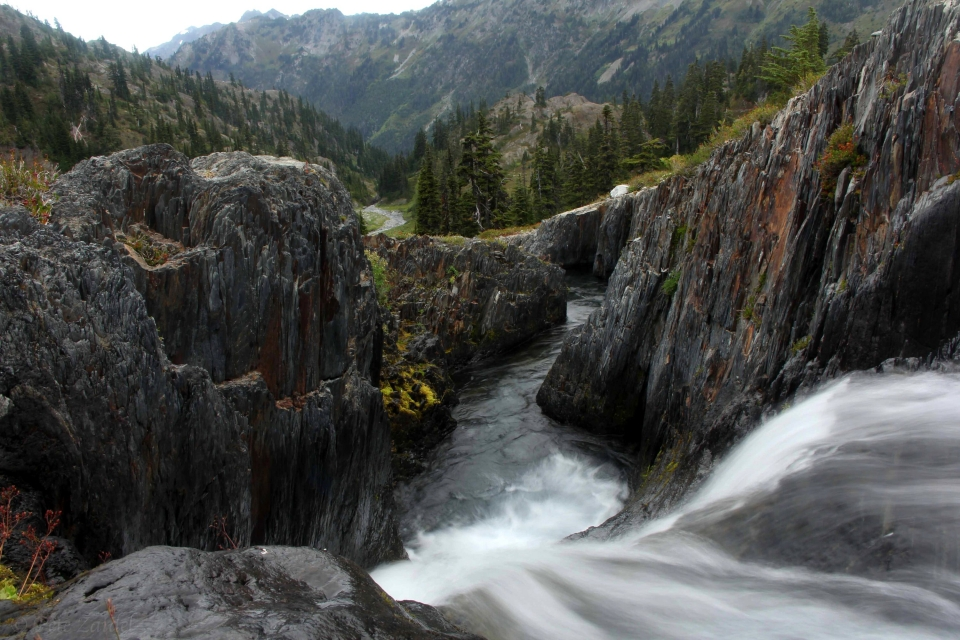 View from the top of a waterfall, surrounded by black rocks and mountains in the horizon at Olympic National Park