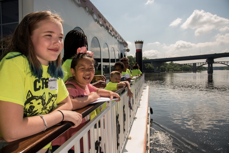 A group of smiling students wearing bright yellow shirts on the side of a ferry boat on the Mississippi National River and Recreation Area