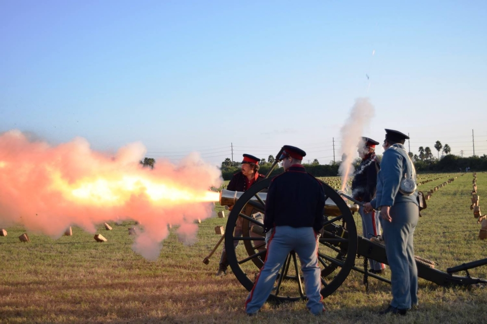 A group of 4 reenactors firing a canon in a sunny field at Palo Alto Battlefield National Historical Park