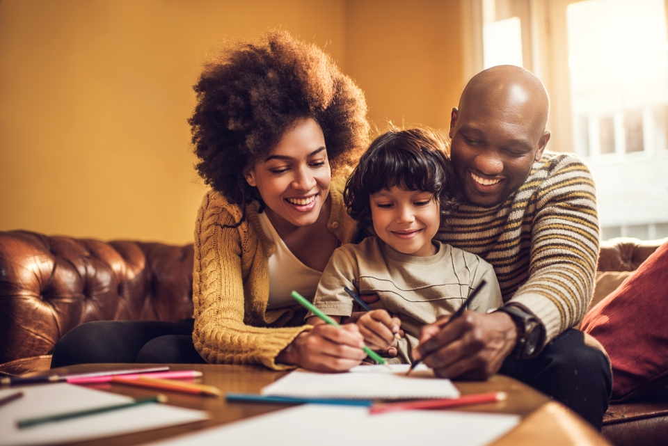 Smiling family having fun while drawing together at home.