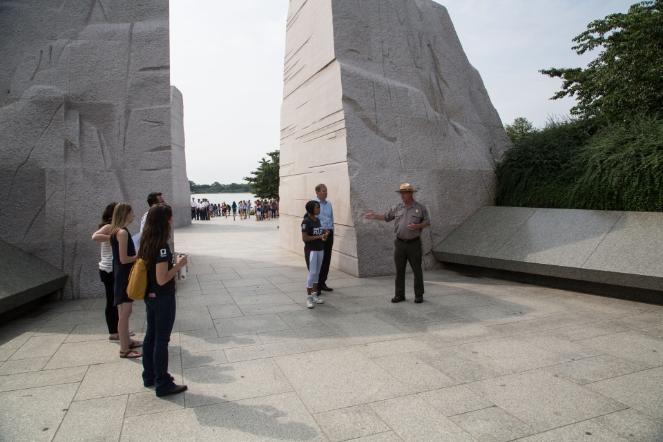 A park ranger talking to a group of people at the marble structures of the Martin Luther King Jr. Memorial