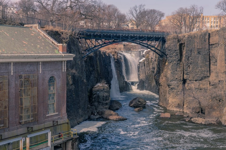 A waterfall cascades down a stone cliff. A brick building is nestled next to the base of the falls, and bridge looms above