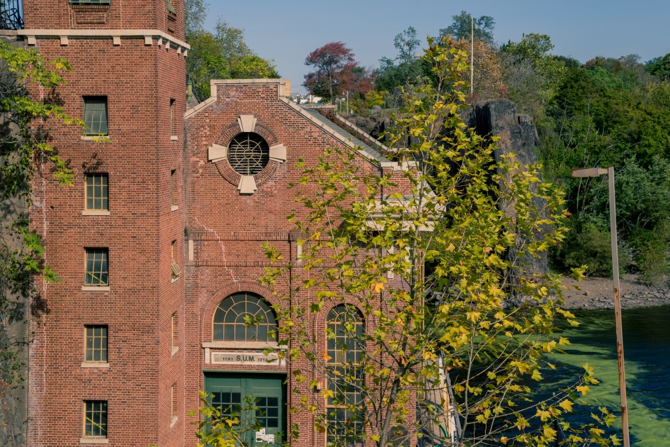 """Multi-story brick power plant building, surrounded by trees. On the door frame, you can read """"SUM"""""""