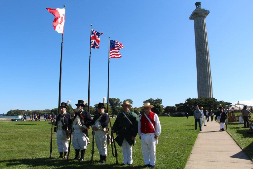 People standing in living history uniforms holding the Canadian, British, and American flag in front of the monument at Perry's Victory & International Peace Memorial