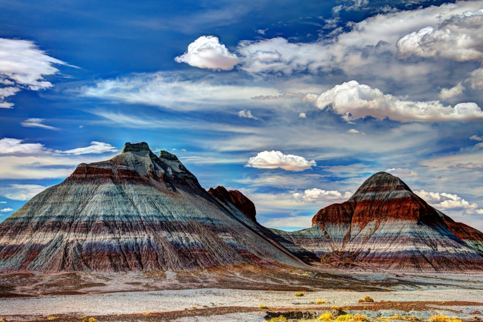 Below a blue sky filled with gentle white clouds, large rock formations display colorful layers in the Tepees area of Petrified Forest National Park.