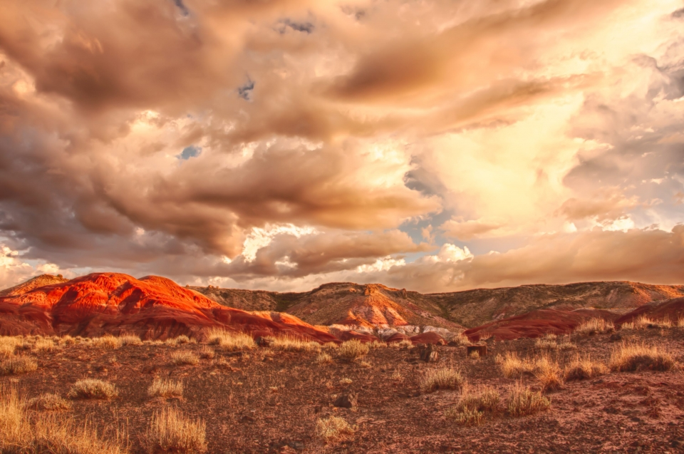 A cloud-filled sky soars over the red and orange hues of Petrified Forest National Park
