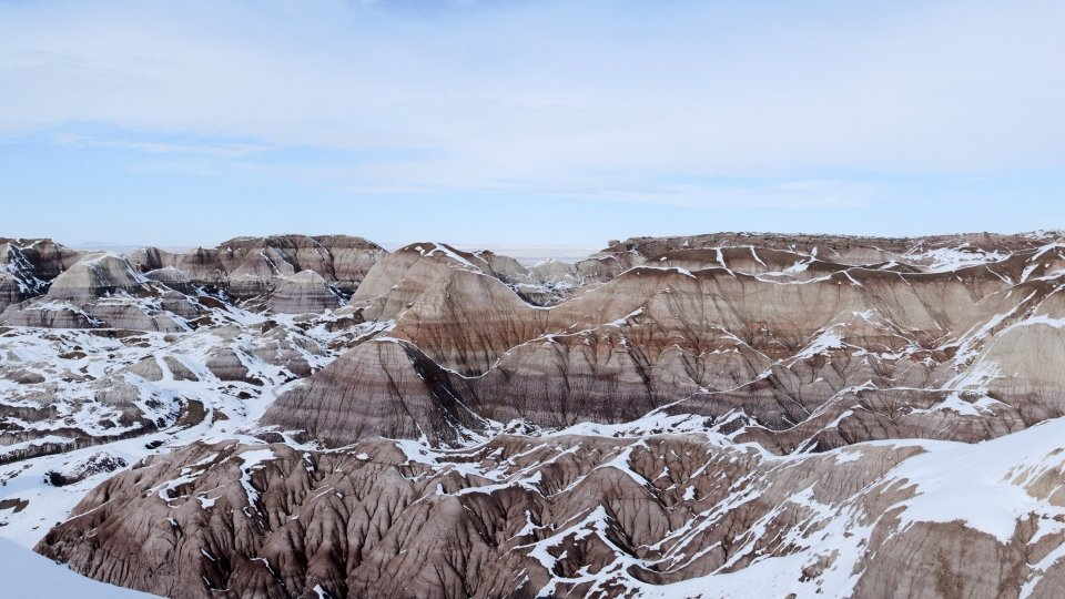A fresh blanket of snow dusts the tops of orange ridges and cliffs