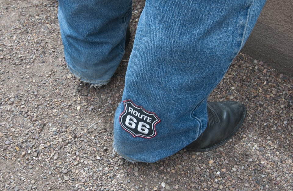 "A patch saying ""Route 66"" on the bottom of a leg of jeans"