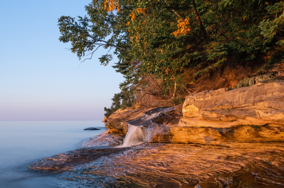 A little flow of water that drops about two feet over a rock ridge on to the rocks and Lake Superior
