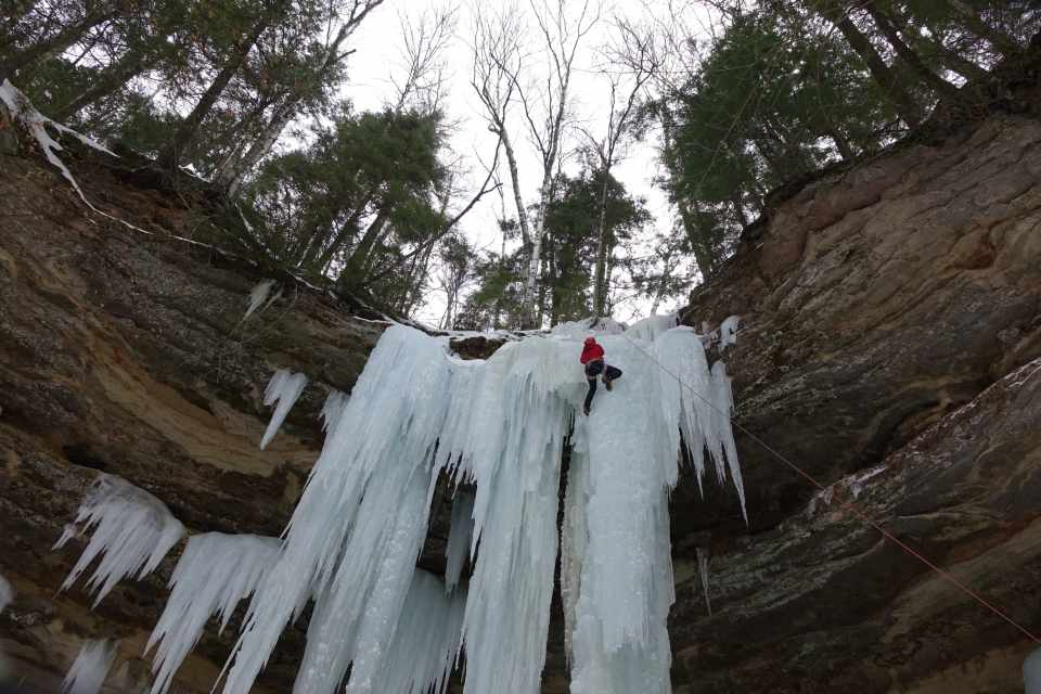 Ice climber near the top of a curtain and column of ice. The ice forms off and out of the sandstone rocks.
