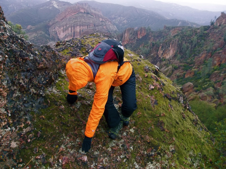 A hiker ascends a high peak at Pinnacles National Park