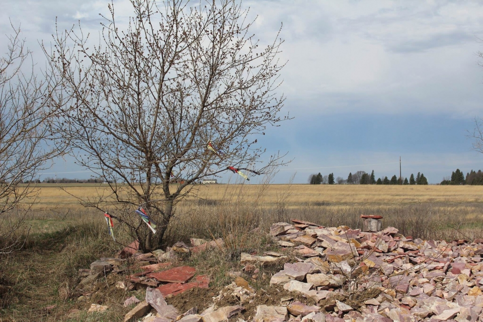 Colorful cloth prayer ties on a tree surrounded by yellow prairie and red quary stones at Pipestone National Monument