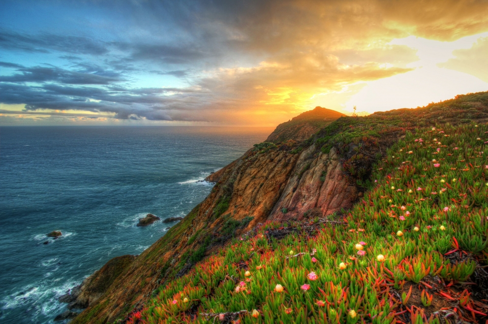 Colorful sunset behind the rocky cliffs of the California coast at Point Reyes National Seashore