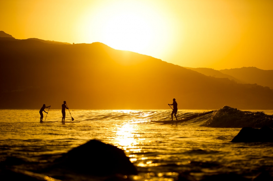 3 people on Stand-Up Paddleboards with the sun rising over the cliffs at Point Reyes National Seashore