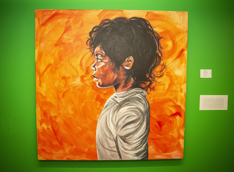 Bright orange painting against a bright green background. Painting of a young woman in a grey sweatshirt looking off to the left.
