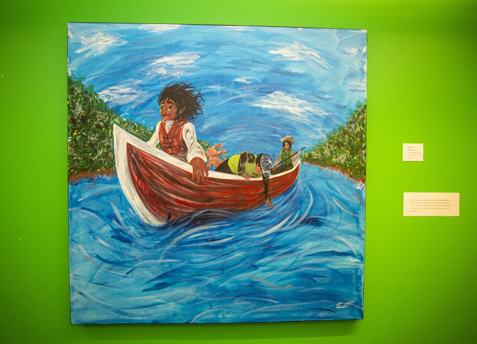 Painting against a bright green wall, depicting a young woman riding in a canoe down a river, wind blowing in her hair.