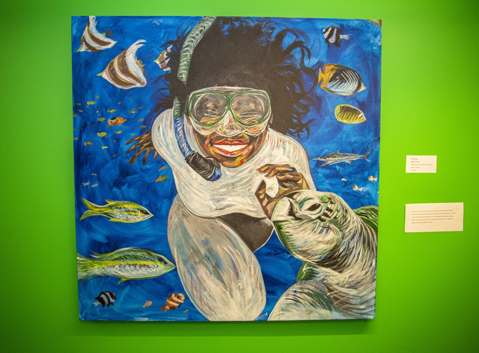 Painting against a bright green wall, depicting a woman snorkeling and smiling. A variety of fish swim around her, and a sea turtle seems to smile in the bottom right corner.