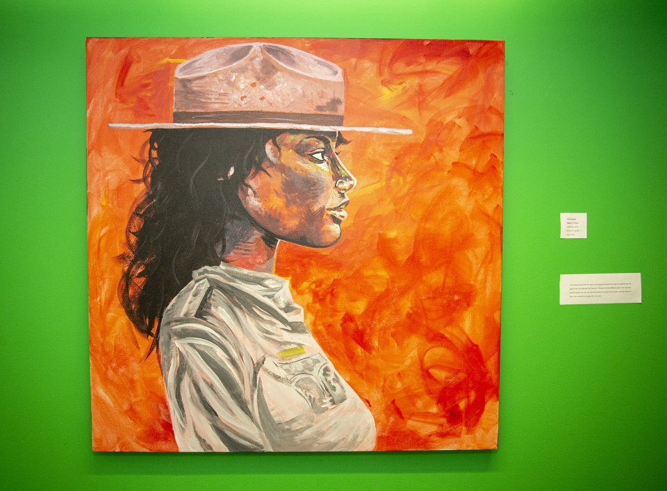 Painting against a bright green wall, depicting a woman in a park ranger uniform and hat, looking to the right.
