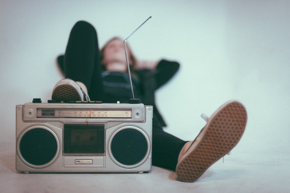 Young woman laying back in repose with her foot in the foreground, rested on an old radio
