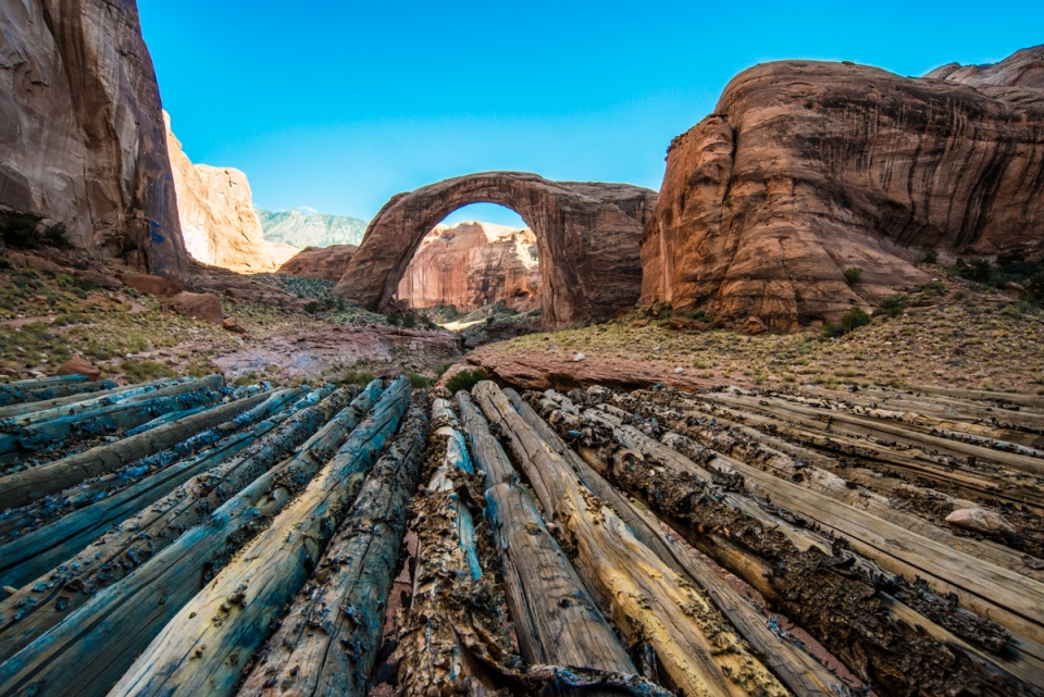 A massive red and brown sandstone arch surrounded by a red dessert landscape at Rainbow Bridge National Monument