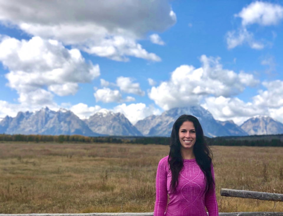 Richelle Dodds stands in a pink sweater. In the background, mountains reach up into a blue sky speckled with fluffy white clouds
