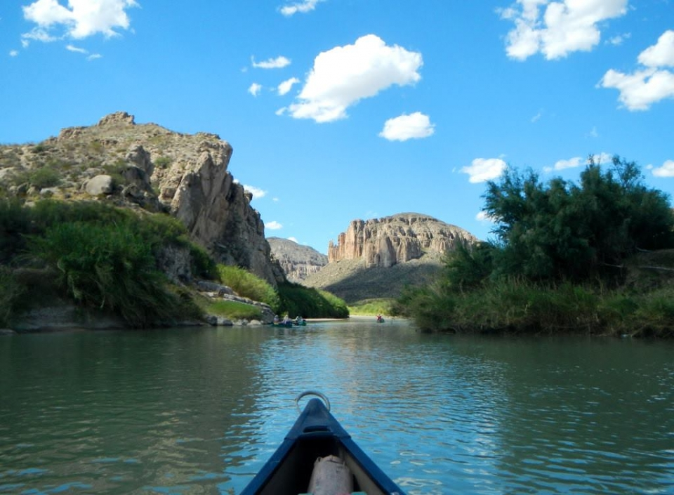 The tip of a canoe looking down Temple Canyon at the Rio Grande National Scenic River