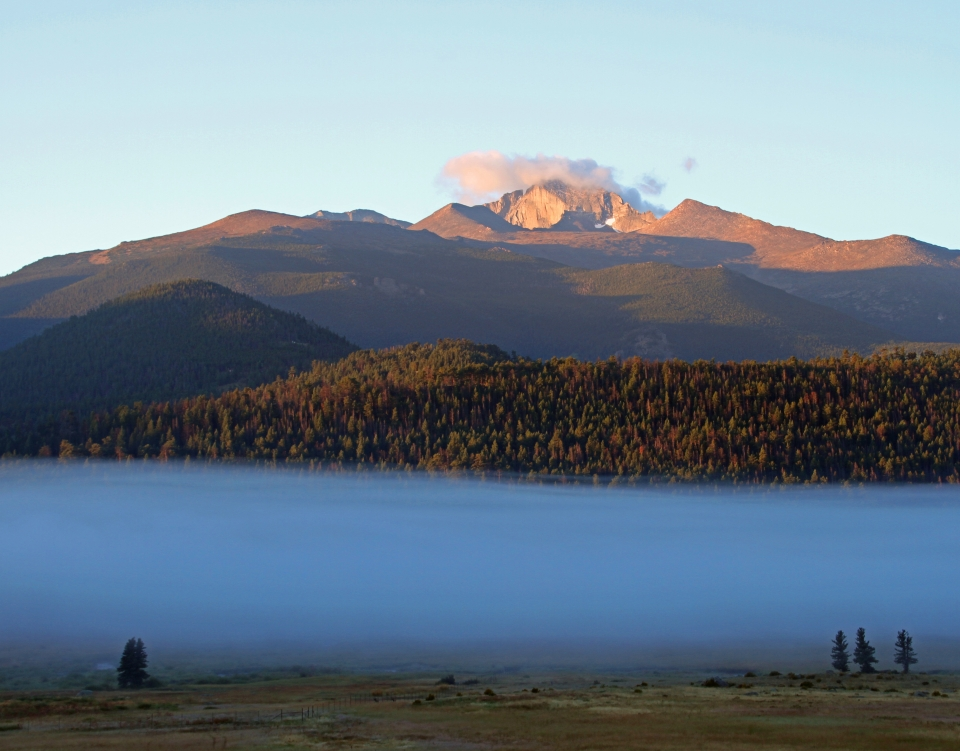 Foggy landscape in front of a sunrise-lit, cloudy Longs Peak in Rocky Mountain National Park