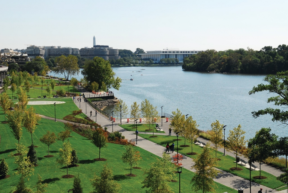The paved walkway and green grasses along the Georgetown Waterfront next to the Potomac with Washington DC in the background