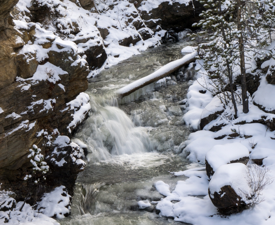 Water cascades down a gentle fall surrounded by snow at Rocky Mountain National Park.