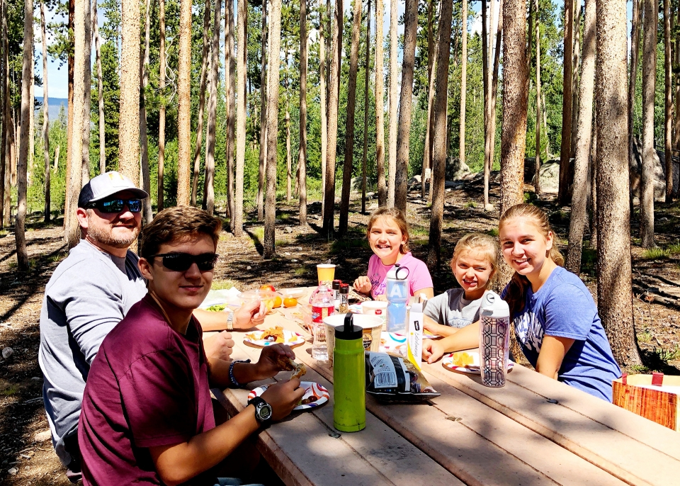 A family sits and enjoys a picnic at a wooden picnic table in a clearing within a forest