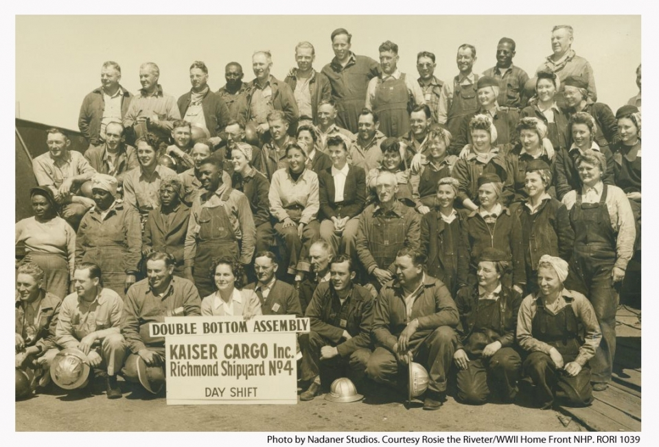 A historic sepia photo of a large group of people, men and women, who worked at the Kaiser Shipyards during World War II