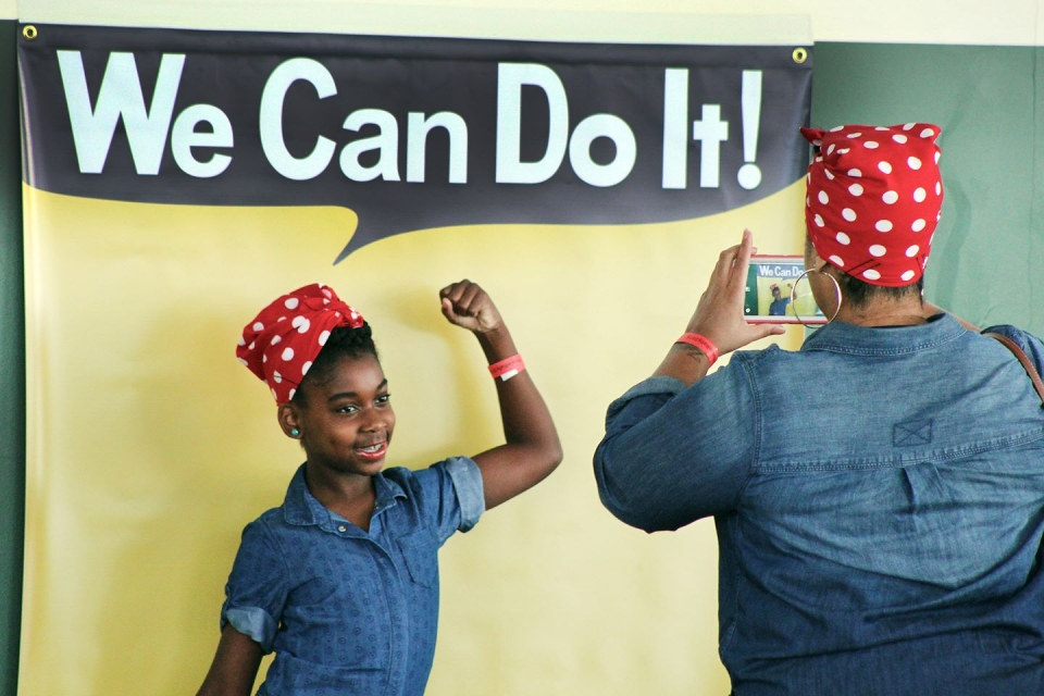 "A woman in a Rosie the Riveter bandana takes a picture of a young visitor also in a bandana in front of a backdrop that says ""We Can Do It!"""