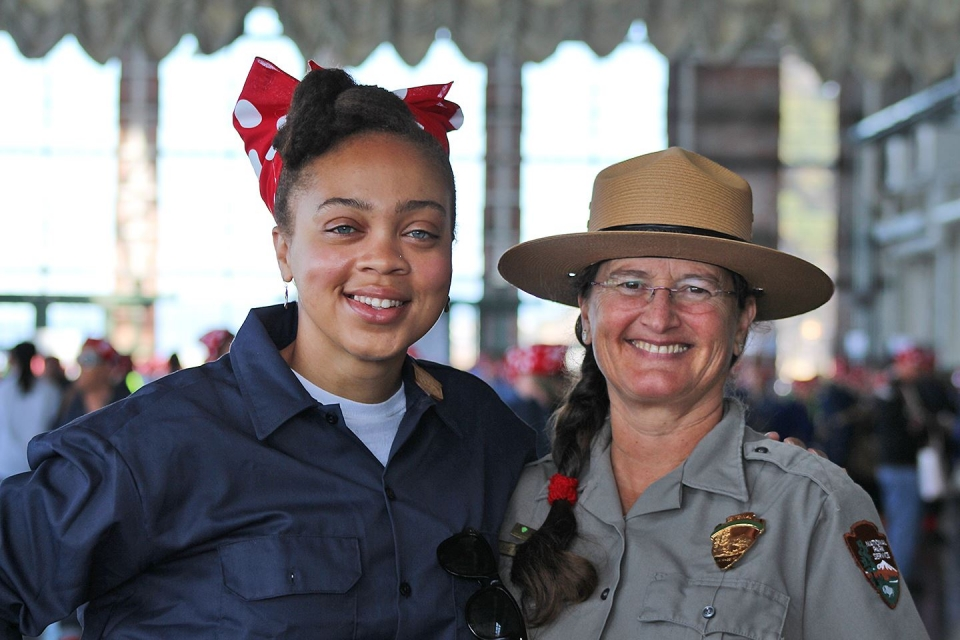 "Two women pose and smile at the camera. One is a park ranger in uniform and the other is dressed like ""Rosie the Riveter"""