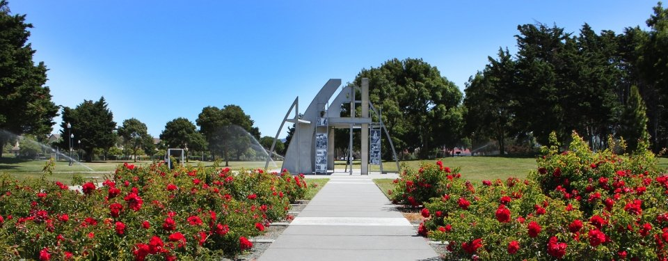 The architecturally modern outdoor memorial surrounded by red flowers and greenery at Rosie the Riveter WWII Home Front National Historical Park.