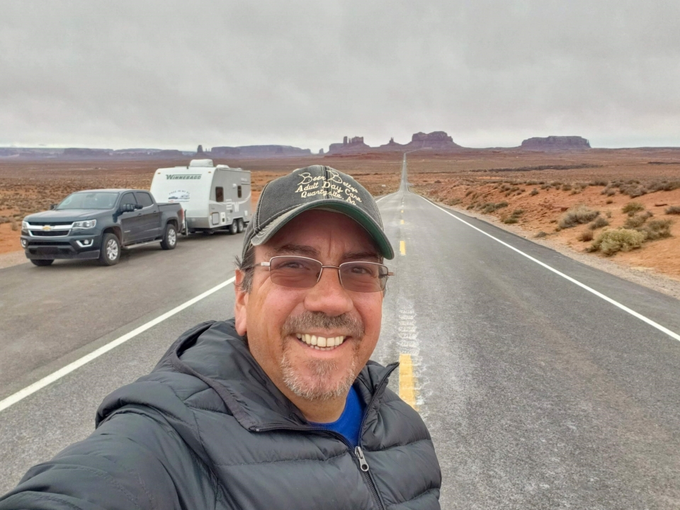 Robert Morales takes a selfie in front of his RV and car on an open road