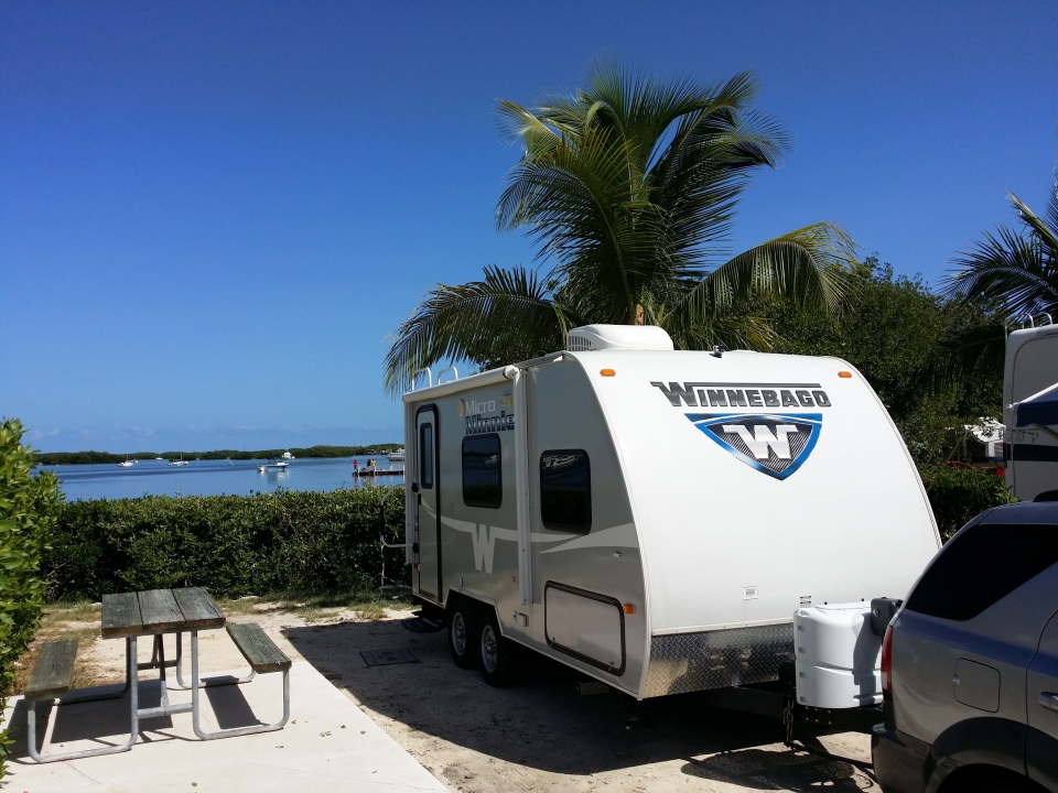 RV set up near a lake, with a Winnebago RV set up next to a picnic table