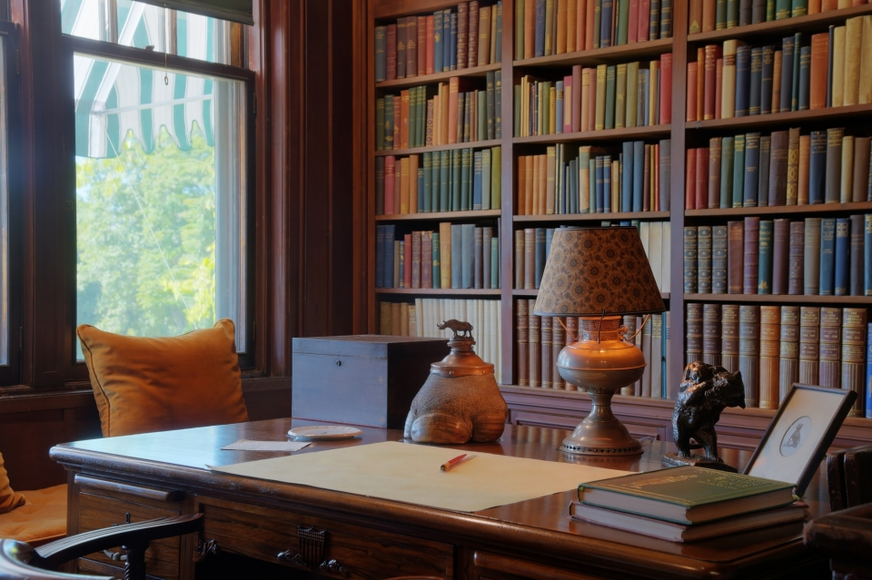 An alcove with a bookcase taking up the right wall. The bookcase is filled with books of different colors. The left wall has tall windows and a window seat bench with orange cushions and pillows. There is a large wooden desk with a box, rhinoceros foot in