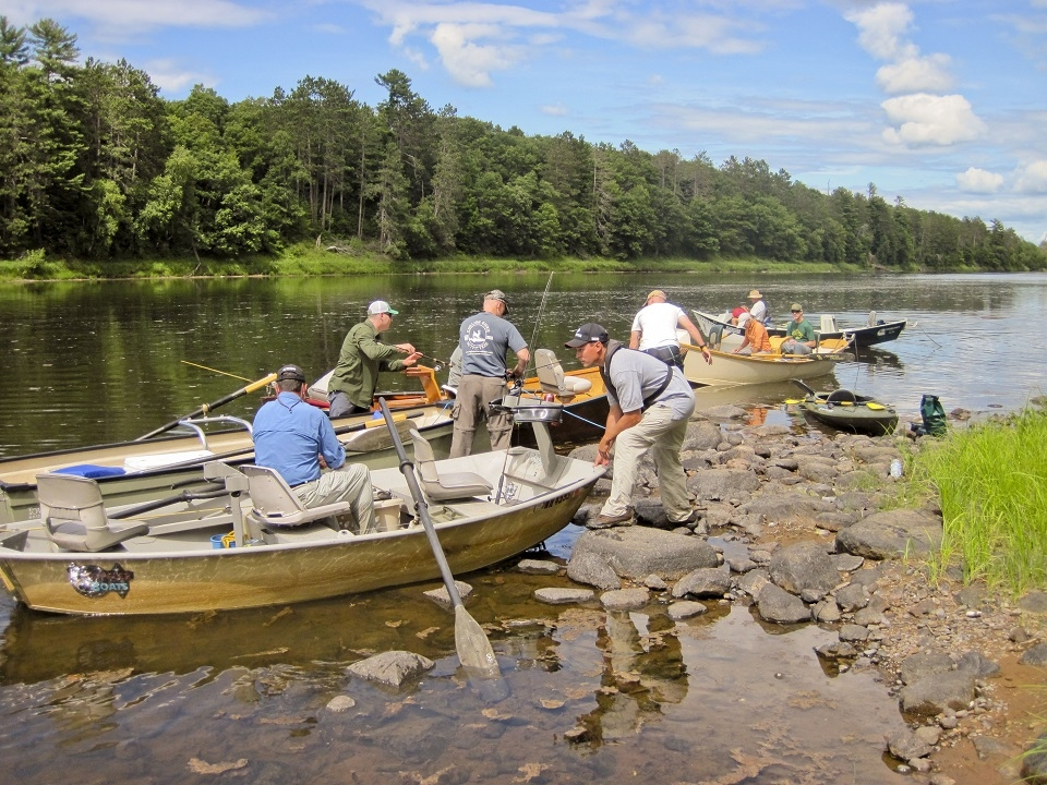 A group of rowboats and a small group of men on the shore of Saint Croix National Scenic River on a clear, calm day with the Vets on the River Program