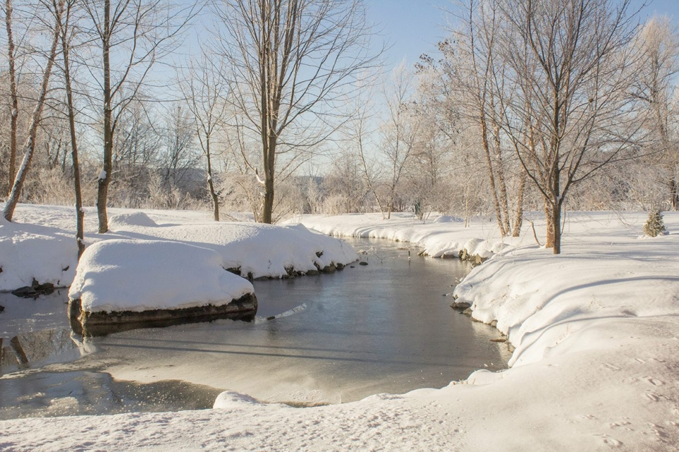 Snow-covered landscape with bare trees and a partially frozen river running down the middle at Saint Croix National Scenic Riverway