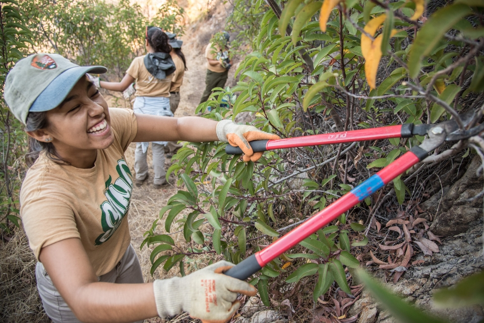Girl laughing and smiling while trimming plants at Santa Monica Mountains National Recreation Area