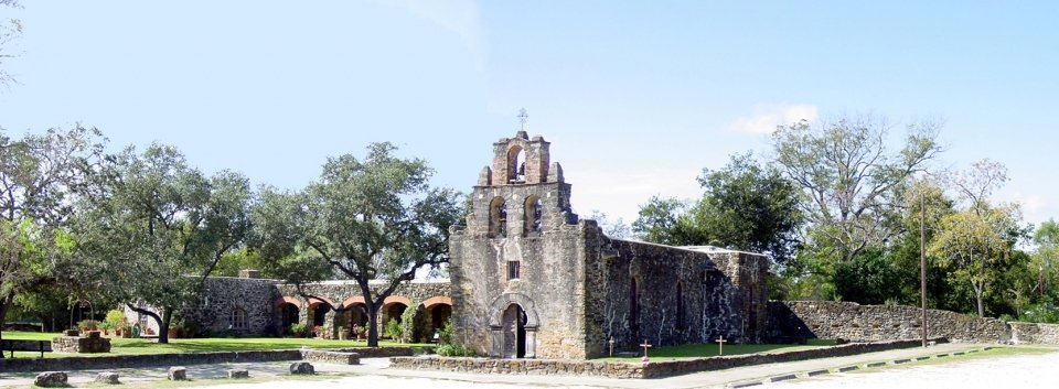 Panoramic view of Mission Espada, a grey stone building surrounded by trees